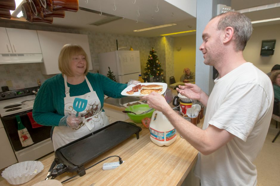 Tony Mathre picks his plate up from Donna Goettler Monday during a Christmas morning breakfast at the Wallingford Emergency Shelter in Wallingford December 25, 2017 | Justin Weekes / For the Record-Journal