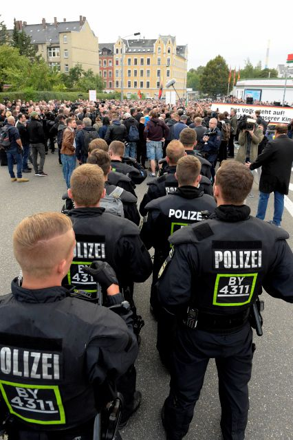 "Police officers secure right wing demonstrators during a far-right demonstration in Chemnitz, Germany, Thursday, Aug. 30, 2018 after a man has died and two others were injured in an altercation between several people of ""various nationalities"" in the eastern German city of Chemnitz last Sunday. (AP Photo/Jens Meyer)"