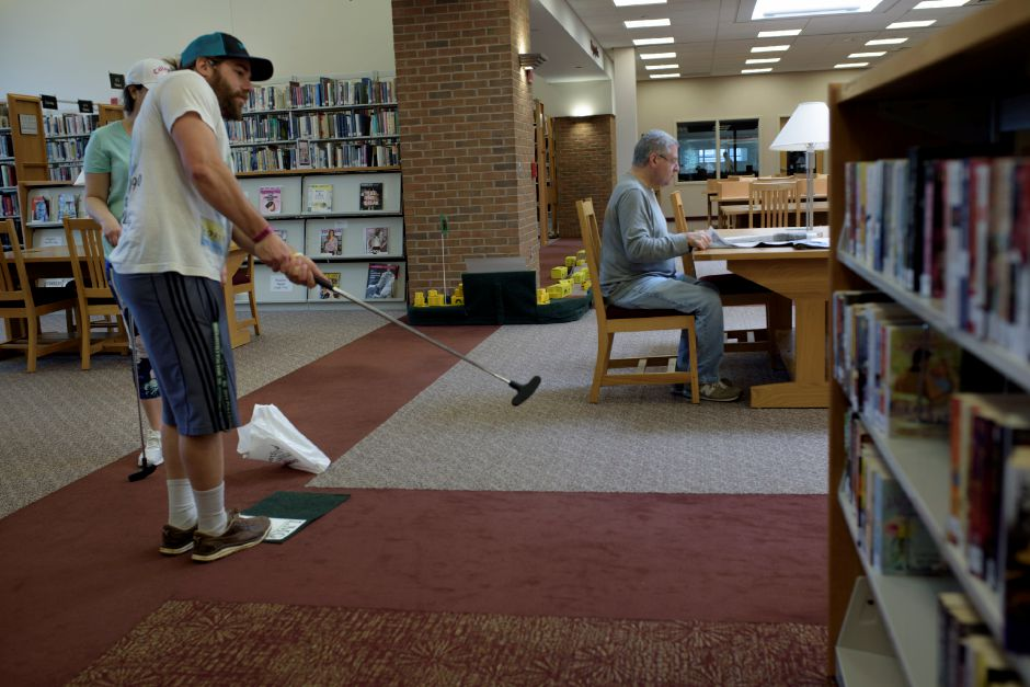 Wallingford residents Ryan Boroski and Michelle Daconto play the course as Art Fritz reads the newspaper Saturday. The Wallingford Public Library set up a mini-golf course  for ages 5 and up. Photos by Monica Jorge, Special to the Record-Journal