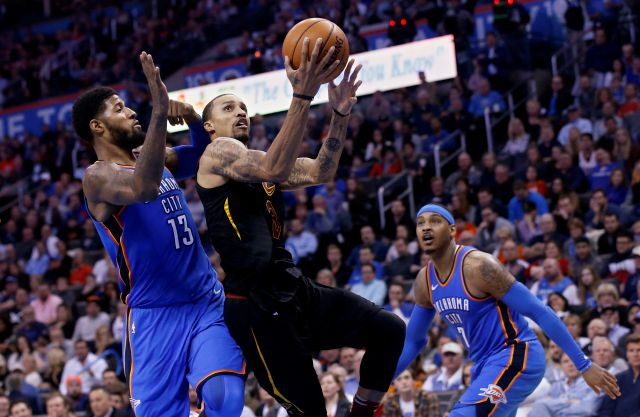 Cleveland Cavaliers guard George Hill (3) shoots between Oklahoma City Thunder forward Paul George (13) and forward Carmelo Anthony (7) during the first half of an NBA basketball game in Oklahoma City, Tuesday, Feb. 13, 2018. (AP Photo/Sue Ogrocki)