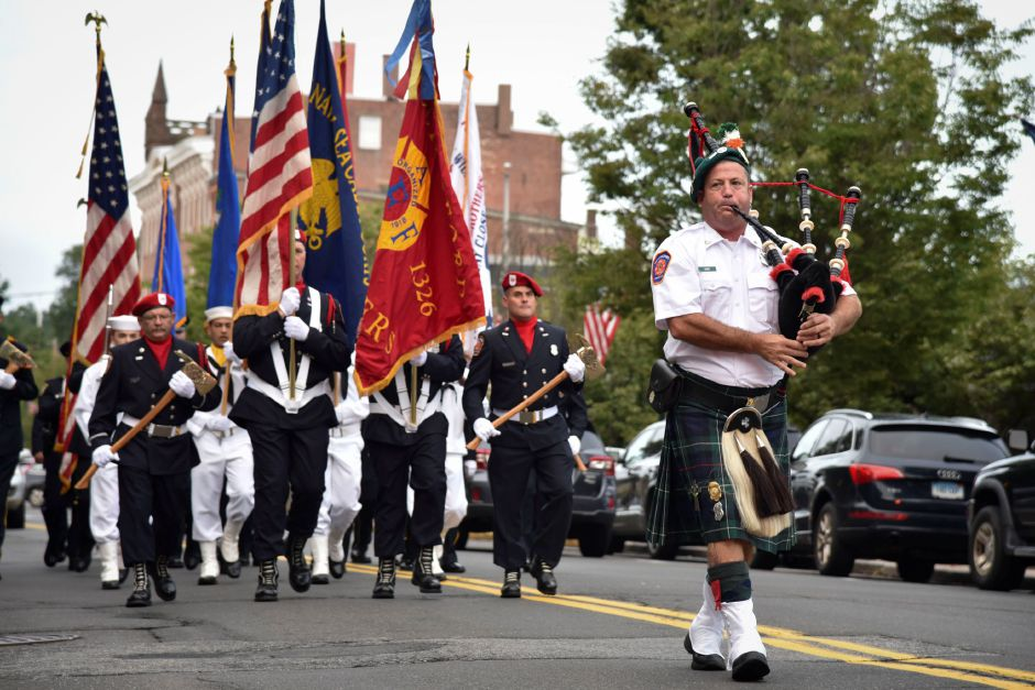 Firefighter David Gade, on bagpipes, leads members of the Wallingford Fire Department, Police Department, color guard and veterans and fraternal organizations