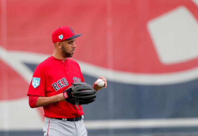 Boston Red Sox starting pitcher David Price looks at a ball as he warms up at the team