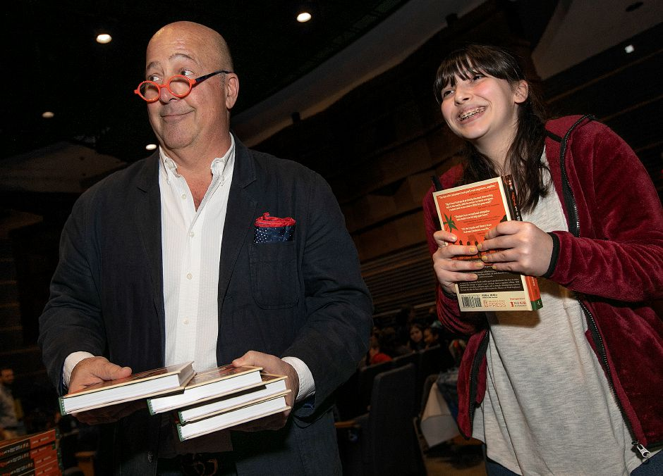 "Washington Middle School eight-grade student Isabelle Chaparro, 14, is all smiles after receiving a signed copy of ""AZ and the Lost City of Ophir"" by author Andrew Zimmern, left, at Platt High School, Wed., May 15, 2019. Zimmern is the globe-trotting host of the ""Bizarre Foods"" TV show. Dave Zajac, Record-Journal"