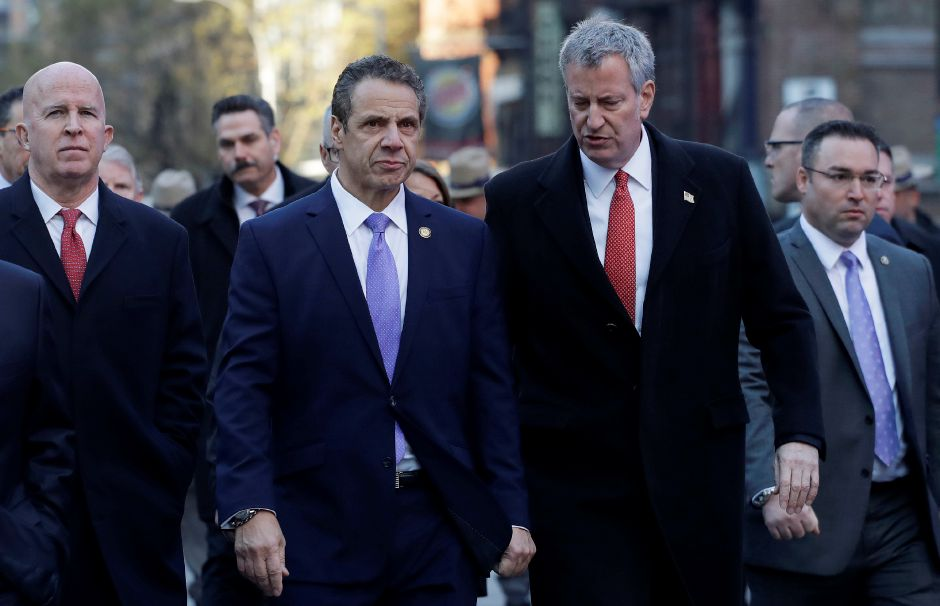 FILE PHOTO: New York Gov. Andrew Cuomo, center, and Mayor Bill de Blasio arrive for a news conference, Monday, Dec. 11, 2017, outside the Port Authority Bus Terminal in New York. Police said a man with a pipe bomb strapped to his body set off the crude device in a passageway under 42nd Street between Seventh and Eighth Avenues. Police Commissioner James O