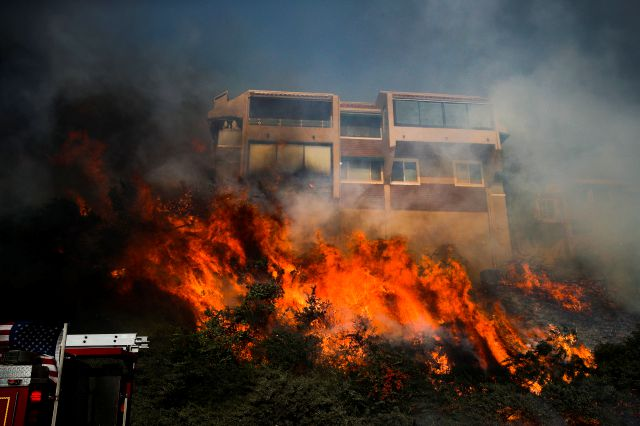 A wildfire threatens a home Tuesday, Dec. 5, 2017, in Ventura, Calif. Ferocious winds in Southern California have whipped up explosive wildfires, burning a psychiatric hospital and scores of other structures. (AP Photo/Jae C. Hong)