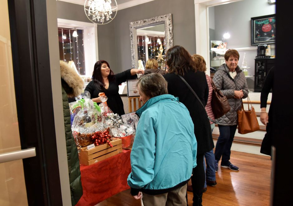 Strollers enjoy free refreshments and discounts at Elite Creations Salon during the 9th annual Holiday Stroll in downtown Wallingford on Friday, Dec. 1, 2017. | Bailey Wright, Record-Journal