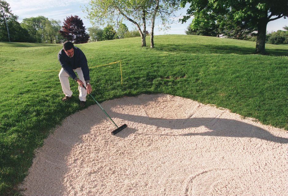 RJ file photo - Paul A. Sabino, golf course superintendent at the Farms Country Club in Wallingford, rakes a sand trap at 7:30 a.m., May 1999.