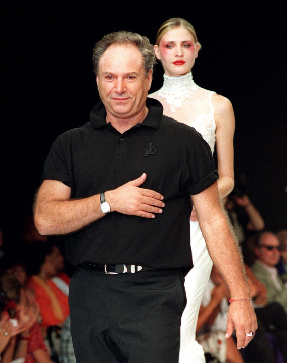 Italian designer Rocco Barocco followed by one of his models, asks the public not to applaude in mourning of Gianni Versace