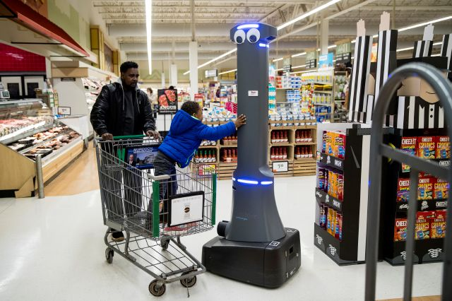 William Rucker and his grandson Justice, 4, say hello to a robot named Marty as it cleans the floors at a Giant grocery store in Harrisburg, Pennsylvania on Tuesday. On Monday, the Carlisle-based Giant Food Stores announced new robotic assistants will be arriving at all 172 Giant stores by the middle of this year. The chain's parent company says it plans to eventually deploy the robots to nearly 500 stores. Matt Rourke,  Associated Press