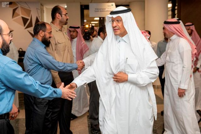 In this Sunday, Sept. 15, 2019, photo released by Saudi Press Agency, SPA, Saudi Energy Minister Prince Abdulaziz bin Salman, center, shakes hands with staff during his visit of the Saudi Aramco plants one day after the attacks in Abqaiq, Saudi Arabia. (Saudi Press Agency via AP)