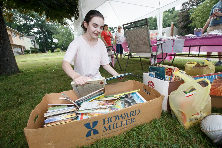 Chelsea Fitgerald 13 sorts through book donations Saturday during the 6th Annual childrens book drive to benefit Read to Grow July 28, 2018 | Justin Weekes / Special to the Record-Journal