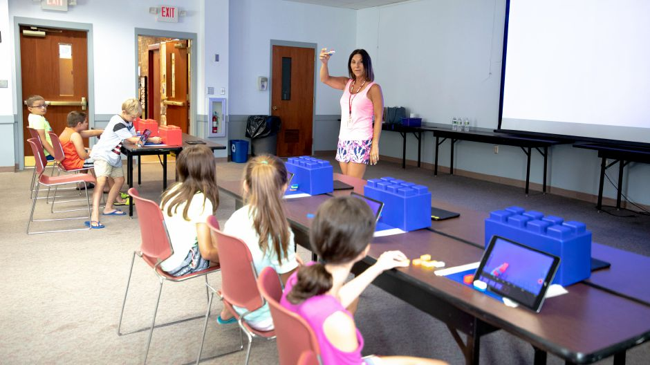 Griswold Elementary School Library Media Specialist Danielle Salina shows a dozen kids what they
