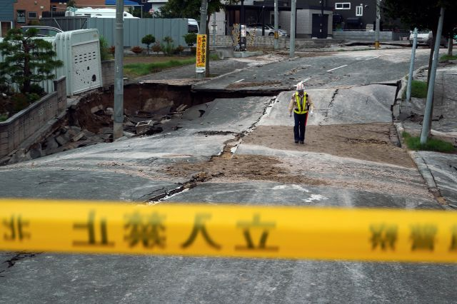 A security guard walks on an earthquake-damaged street in Kiyota, outskirts of Sapporo city, Hokkaido, northern Japan, Friday, Sept. 7, 2018. A powerful earthquake hit wide areas on Japan