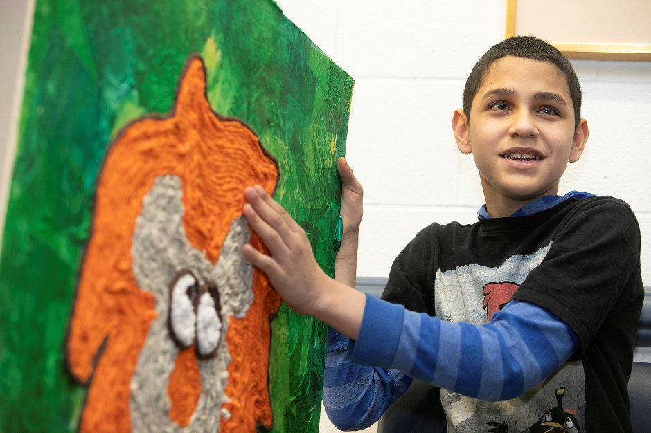Sixth-grade student Jose Nieves Roman, 12, who is blind, talks about his art project featuring a lion made from mixed media at Lincoln Middle School in Meriden on Tuesday. Roman used yarn of different textures in creating the project over a two-month period. Dave Zajac, Record-Journal