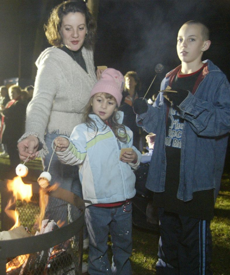 Nicole Arsenault, left, and her daughter, Kelsey Thomas, 6, and son, Brandon Thomas, 12, roast marshmellows and make smores at the Christmas festival in Hubbard Park on Dec. 12, 2006.