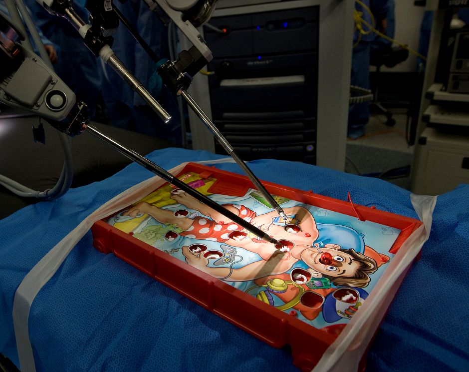 Robotics students from Southington High School maneuver a DaVinci robot while removing pieces from an Operation game board in an operating room at MidState Medical Center in Meriden, Monday, December 16, 2013. | Dave Zajac / Record-Journal