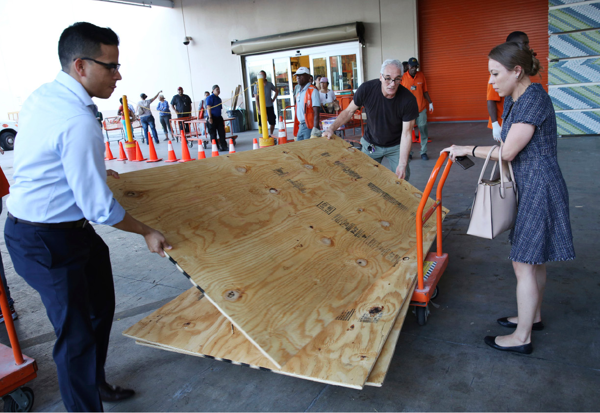 Carla Perroni Aguilera of Miami Beach, Fla., holds a cart as her husband Ronald Aguilera and her father Joe Perroni load sheets of plywood at The Home Depot store in North Miami, Fla., Wednesday, Sept. 6, 2017. Florida residents are preparing for the possible landfall of Hurricane Irma, the most powerful Atlantic Ocean hurricane in recorded history. (AP Photo/Marta Lavandier)