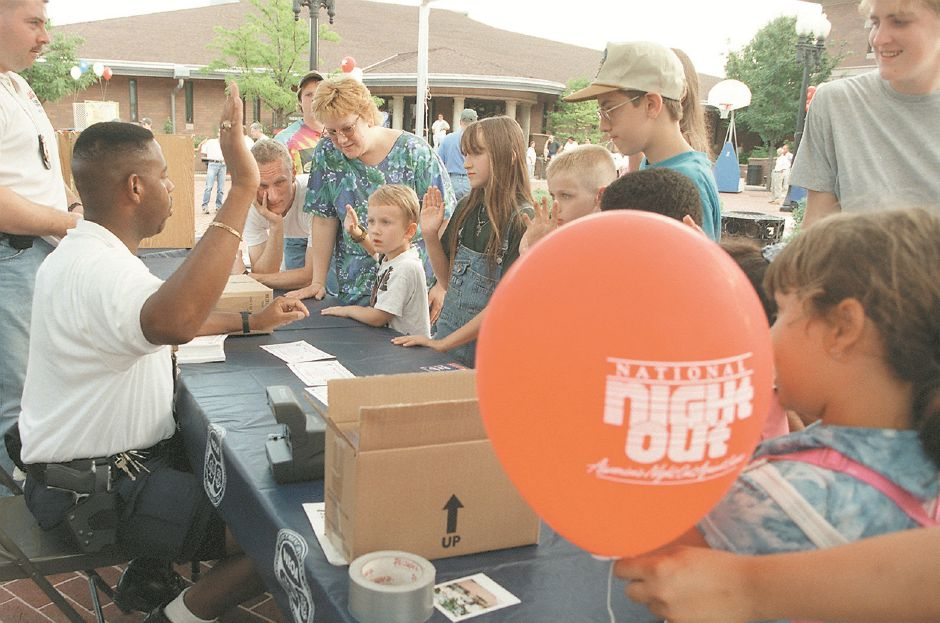 RJ file photo - Meriden Police Officer Glenn Felton, left, swears children to be good and not use drugs at the Narcotics Enforcement Officers Association booth during the National Night Out Aug. 4, 1998.