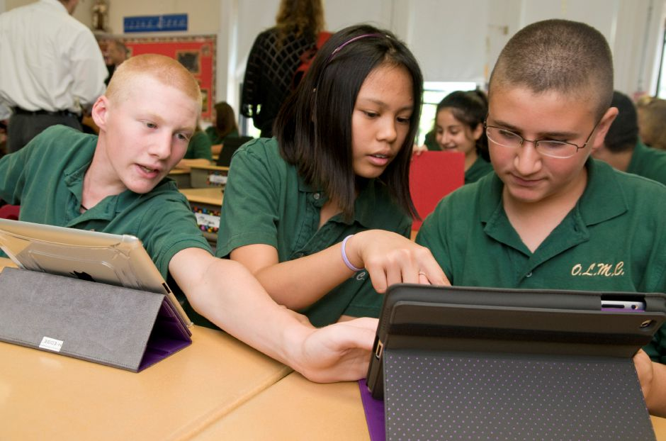 From left: Eighth graders Benjamin Logan and Alyssa Barandon show fellow student Nico Nigro how to use an application on his iPad during class at Mount Carmel School in Meriden, September 14, 2011. (Sarah Nathan/Record-Journal)
