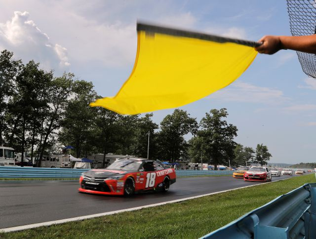 A caution flag waves as Ryan Preece (18) and the pack pass on wet pavement after a rain shower on the back straightaway during a NASCAR series auto race, Saturday, Aug. 4, 2018, in Watkins Glen, N.Y. (AP Photo/Julie Jacobson)