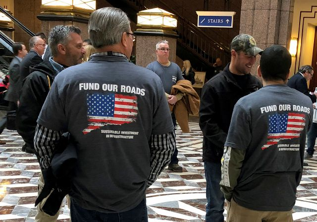 Members of The International Union of Operating Engineers, Local 478, wear shirts supporting tolls for road funding as hundreds of people on both sides of the issue turned out Wednesday, March 6, 2019, for a legislative hearing at the Capitol in Hartford, Conn., on whether Connecticut should institute electronic highway tolls. The turnout highlighted the strong divide that