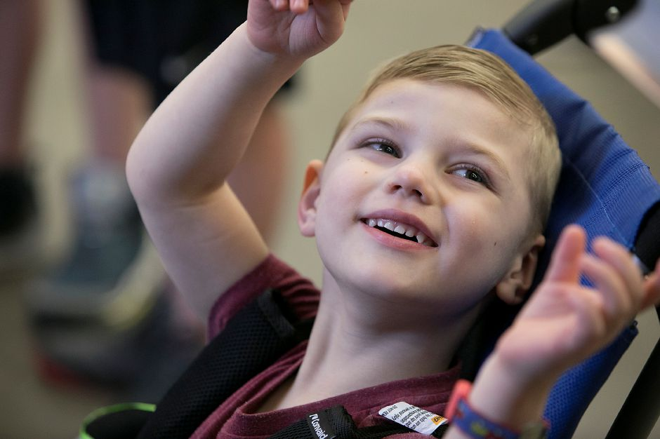Henry Curylo, 4, of Southington, smiles while waiting for his electric car to be finished by students at Southington High School Friday, May 11, 2018. Students from Southington High School and Central Connecticut State University made the final fittings to battery-powered cars for two special needs children. Dave Zajac, Record-Journal