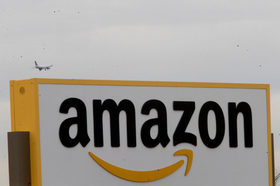 In this Wednesday, Dec. 5, 2018, an airplane flies over the Amazon sign at the Amazon fulfillment center on Staten Island borough of New York. (AP Photo/Mary Altaffer)