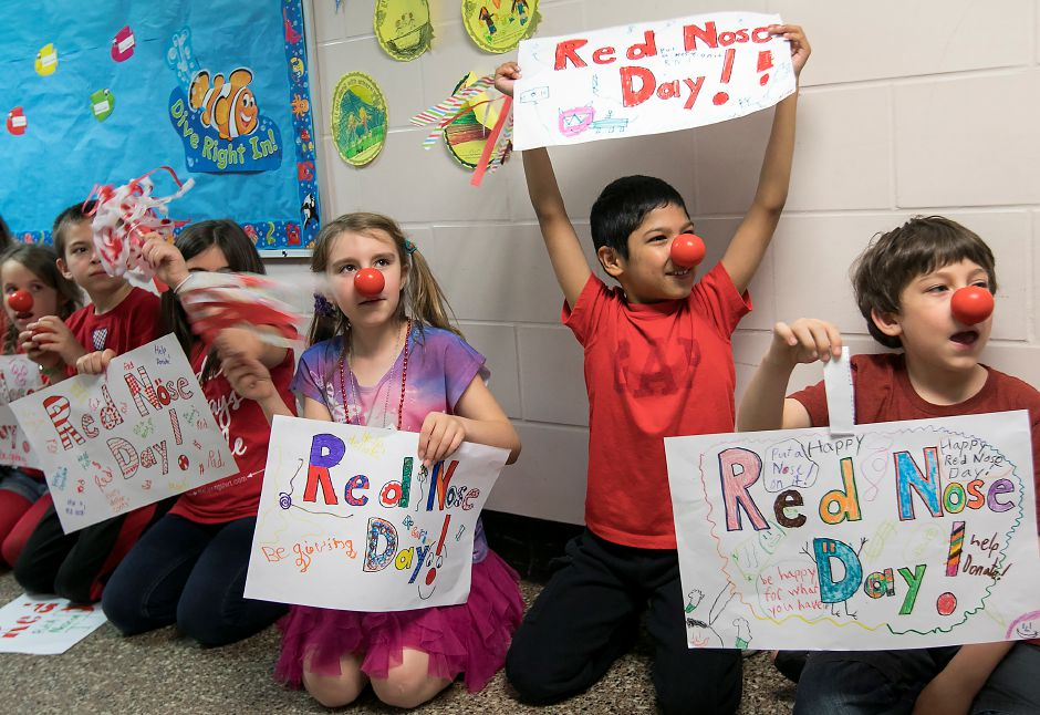 Second-grade student, Noe Garcia, 8, holds his sign high during a Red Nose Day parade at Stevens School in Wallingford, Thursday, May 25, 2017. | Dave Zajac, Record-Journal
