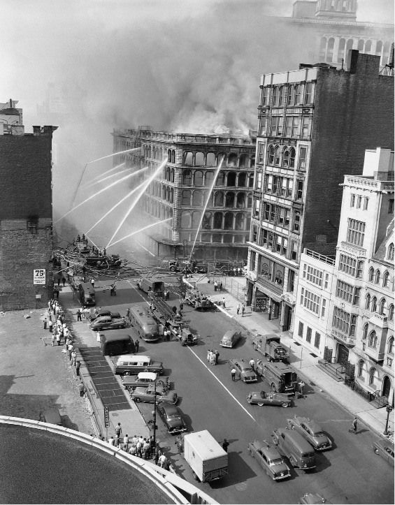 Eight streams of water are directed against the shell of the former Wanamaker Department Store in downtown Manhattan, New York on July 16, 1956 as firemen fight to contain blaze which burned out of control for 25 hours. Floods of water poured on the blaze resulted in suspension of subway service to two lines in the vicinity. The lines connect Manhattan and Brooklyn and disruption of service will affect thousands of workers. (AP Photo)
