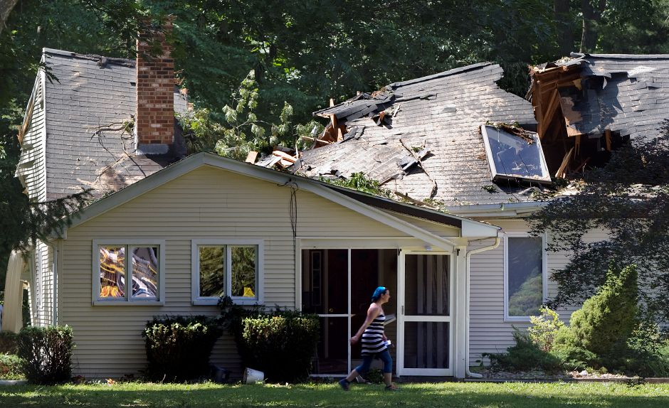 Jen McClure, of Wallingford, walks past her home on Grantham Rd Friday, June 26, 2015 after it was heavily damaged by Tuesday