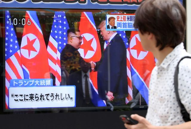 "A man looks at a TV screen showing North Korean leader Kim Jong Un, left, and U.S. President Donald Trump shaking hands before their meeting in Singapore, in Tokyo, Tuesday, June 12, 2018. Japanese letters read: ""Happy to come here."" (AP Photo/Koji Sasahara)"