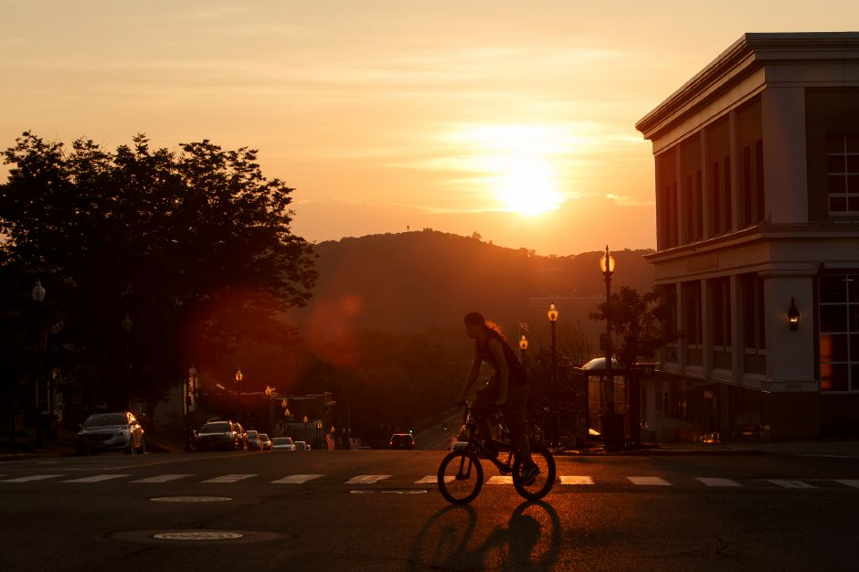 A bicyclist crosses the intersection of Center Street and South Main Street Monday after the second day of heat and humidity forcasted ofr the week July,2 2018 © 2018 Justin Weekes | Special to the Record-Journal