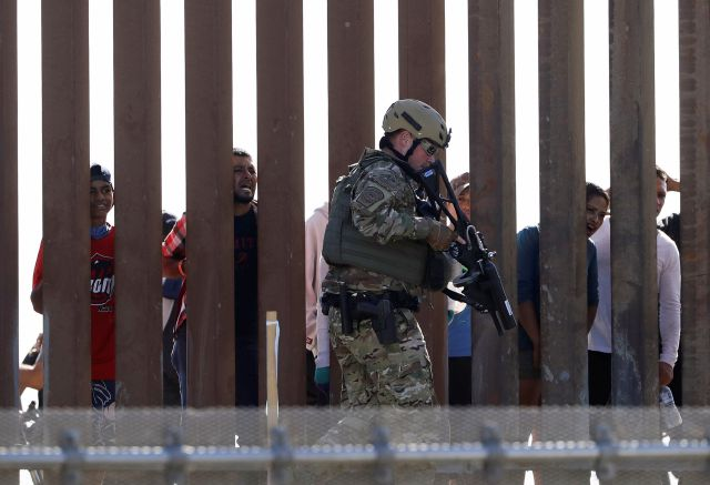 U.S. Customs and Border Protection officers walks along a wall at the border between Mexico and the United States, as seen from San Diego on Sunday, Nov. 25, 2018. Migrants approaching the U.S. border from Mexico were enveloped with tear gas Sunday after a few tried to breach a fence separating the two countries. The Border Patrol office in San Diego said via Twitter that pedestrian crossings have been suspended at the San Ysidro port of entry at both the East and West facilities. All northbound and southbound traffic was halted. (AP Photo/Greg Bull)