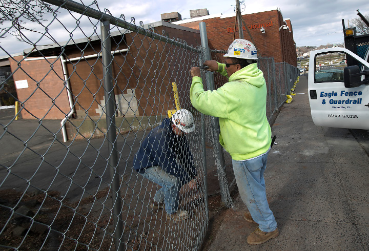 Workers for Plainville based Eagle Fence & Guardrail, James Turcotte, left, and Luis Cora, right, secure fencing around the former Record-Journal building at 11 Crown St. in Meriden, Tuesday, February 28, 2017.  | Dave Zajac, Record-Journal