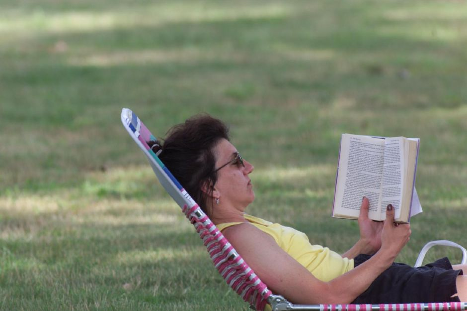 "Carla Danajovits of Cheshire reads a novel called ""Vegas Sunrise,"" by Fern Michaels. She was enjoying the shade tree at Recreation Park in Southington, Aug. 1999."