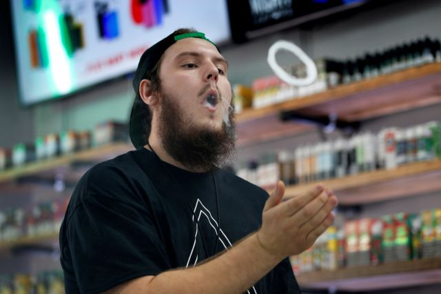 In this Tuesday, Sept. 3, 2019, photo, Devin Lambert, the manager at Good Guys Vape Shop, demonstrates to blow a vapor ring while using an e-cigarette in Biddeford, Maine. Efforts to ban flavored e-cigarettes and reduce their appeal to youngsters have sputtered under industry pressure in over a half-dozen states this year. The industry and its lobbyists urged lawmakers to leave mint and menthol alone. A proposed ban that President Donald Trump outlined Wednesday, Sept. 11, would...