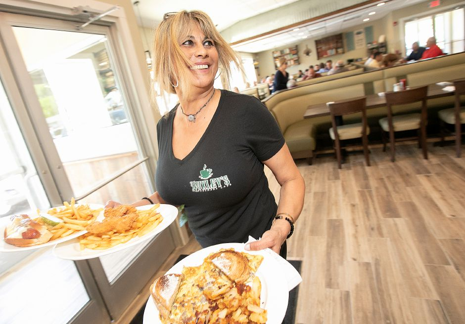 Waitress Stephanie Papadopoulos carries orders to customers at the new Huxley