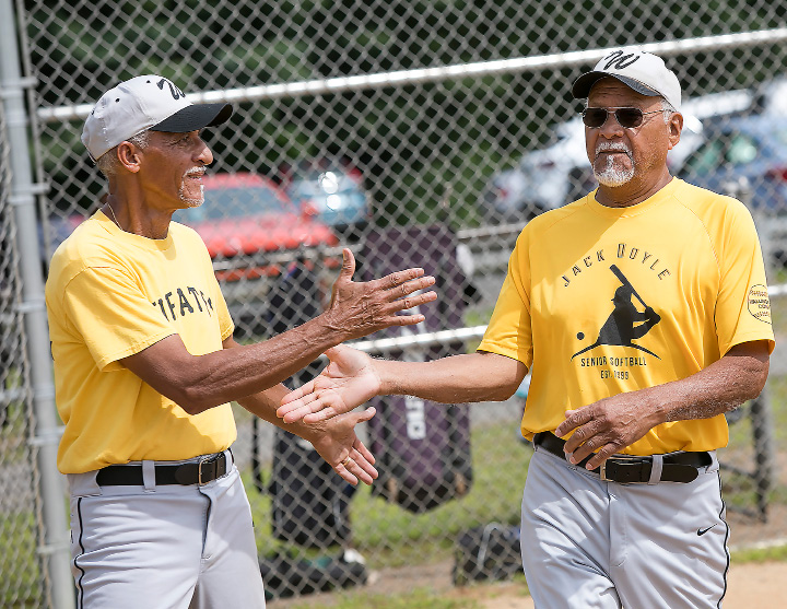 Jaime Felix, 72, of Guilford, left, greets teammate, German Velez, 78, of New Haven, right, after scoring a run during a Jack Doyle senior softball league game at Pragemann Park in Wallingford, Monday, August 14, 2017. The Naturals defeated the Pirates 15-10. | Dave Zajac, Record-Journal