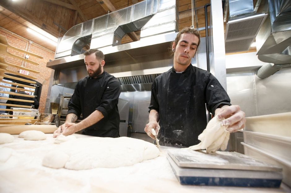 Chris Jolly left and Jon Crystal portion pizza dough Saturday at Sauced at Kinsmen in the Kinsmen Brewery in Southington February 10, 2018 | Justin Weekes / Special to the Record-Journal