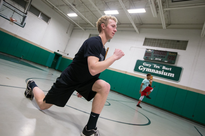 At left, Devon Gardner, 16, reaches to catch a tennis ball in a speed drill as Washington Nationals farmhand Jack Sundberg looks on. Below,Cameron Germe runs through a stretching drill.| Photos by Justin Weekes, Special to the Record-Journal