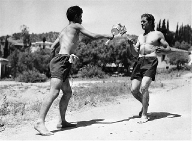 The flaming Olympic Torch began its journey to Wembley Stadium in London, United Kingdom  and the 1948 Olympic Games, from Olympia, near Katakolon, Greece on July 17, 1948. After being ignited by the rays of the sun in Olympia stadium, thirty fleet-footed Greek youths, recruited from local villages, relayed the flaming brand to Katakolon, a seaport town on the Ionian Sea. In this image the Olympic flame reaches one of the thirty relay points on its way from Olympia stadium to the Ionian Coast. The runner at right kindles the torch of fresh runner at left. (AP Photo/Chakales)
