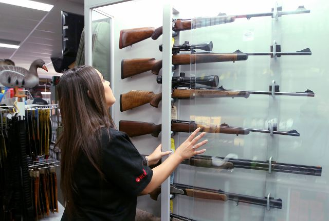 FILE - In this Wednesday, Oct. 4, 2017 file photo, a salesperson checks rifles in a gun shop display in Sydney, Australia. A documentary aired in March 2019 by Al Jazeera reported officials with Australia