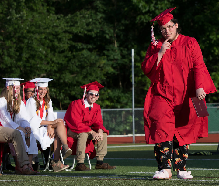 Above, graduate Ryan Clements earns a few laughs from fellow classmates while donning his mom's pig slippers and AC/DC pajamas under his gown during graduation ceremonies Wednesday at Cheshire High School.  | Photos by Dave Zajac, Record-Journal