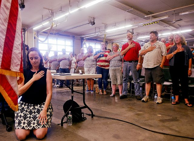 Selectwoman Melissa Schlag kneels for the Pledge of Allegiance during a Haddam, Conn., board of selectmen meeting on Monday, July 30, 2018 at the Haddam firehouse. Protestors and supporters gathered Monday night around a Haddam Town Meeting to address the recent controversy generated by Schlag