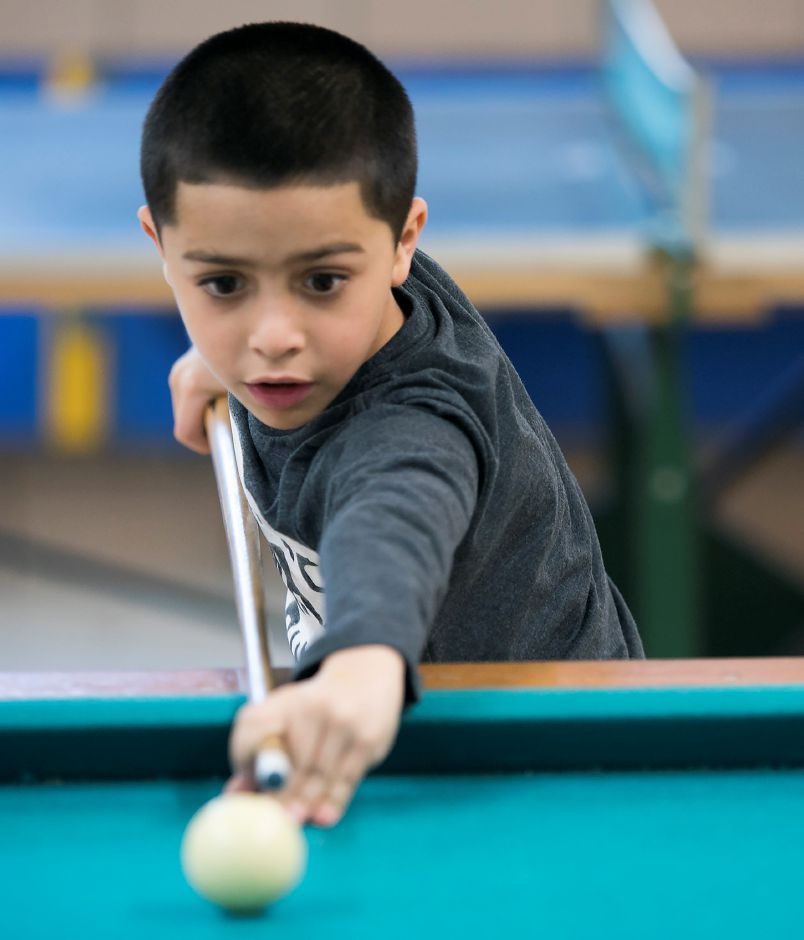 Sebastian Rosario, 7, of Meriden, lines up a shot while playing pool at the Boys and Girls Club in Meriden, Wednesday, Nov. 29, 2017. Local nonprofits are calling on Congress to reject aspects of the proposed tax reform bill that address changes in charitable giving deductions and non-profit status. Dave Zajac, Record-Journal