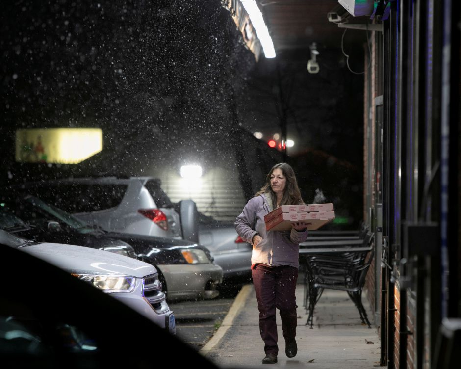 Shelley McQuade, of Meriden, picks up pizza from Sals Appiza on East Main Street as the snow begins to fall in Meriden, Thurs., Nov. 15, 2018. Dave Zajac, Record-Journal