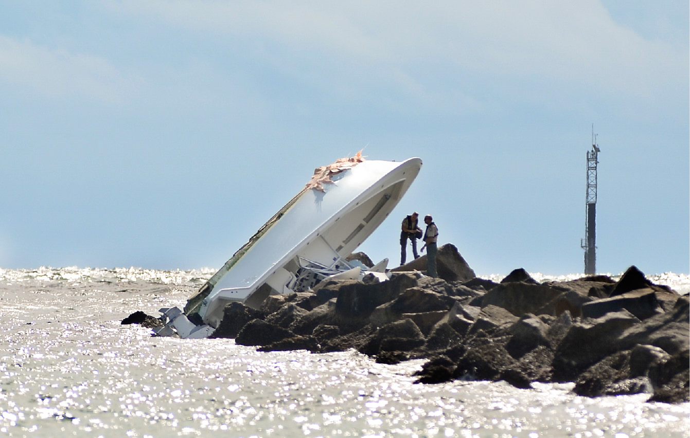 "FILE - In this Sept. 25, 2016, file photo, investigators inspect an overturned boat as it rests on a jetty after a crash off Miami Beach, Fla. Miami Marlins pitcher Jose Fernandez was the ""probable"" operator of a speeding boat that crashed into a Miami Beach jetty on Sept. 25, 2016, killing the star baseball star and two other men, according to a report issued Thursday, March 16, 2017, by the Florida Fish and Wildlife Conservation Commission, which investigated the accident.  (AP Photo/Gaston De Cardenas, File)"