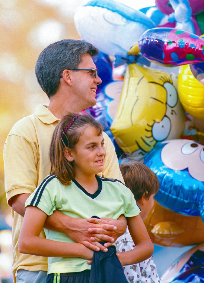 RJ file photo - Meghan Braziel, center, 10, her dad, Tim, and sister, Alexis, 7, take in the sights on the last day of the Apple Harvest Festival in Southington Oct. 11, 1998.