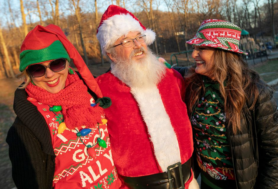 Meriden Parks and Recreation Coordinator Kathy Matula, left, and Pamela Fuschino, facilities coordinator, share smiles with Santa played by Bob McEvoy, of Watertown, during a Parks and Recreation Department hosted ugly holiday sweater party at Hubbard Park in Meriden Fri., Dec. 7, 2018. Dave Zajac, Record-Journal