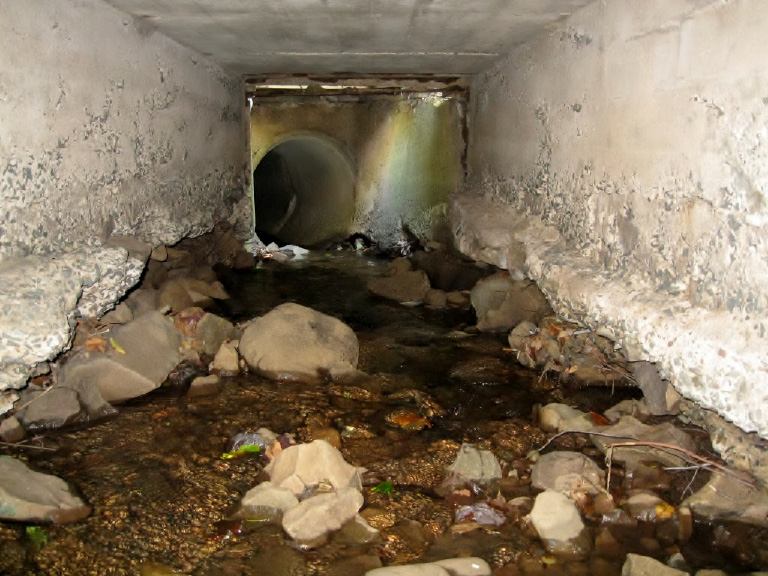 Concrete has worn away at the lower part of the walls of a Lake Beseck culvert, resulting in sinkholes and increased sediment in the lake. Middlefield hopes to receive a STEAP grant to improve the area